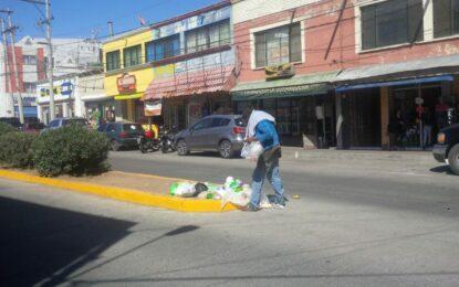 Hombre busca alimento en la basura, en el centro de la ciudad